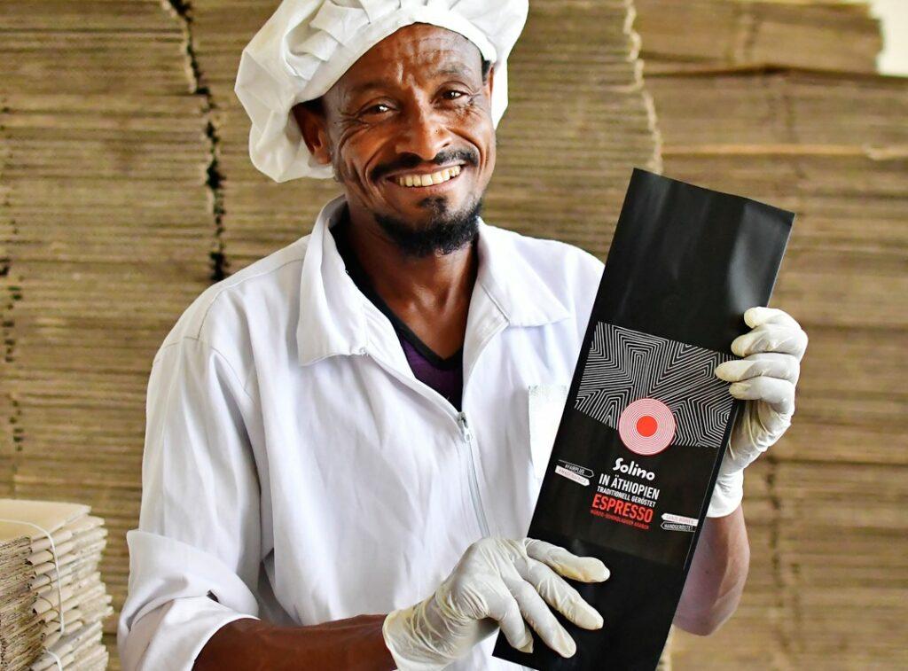 Äthiopischer Kaffeeproduzent hält lachend ein Päckchen Solino Coffee in die Kamera.