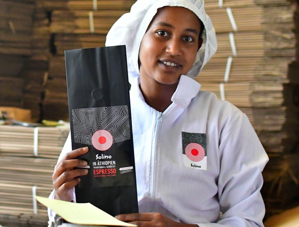 Äthiopische Kaffeeproduzentin hält lachend ein Päckchen Solino Coffee in die Kamera.