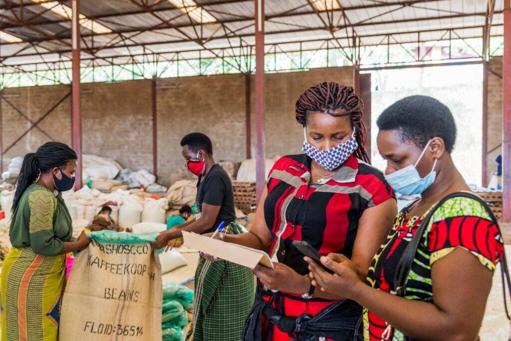 Zwei Frauen schauen auf ein Handy. Die Linke Frau hält Zettel und Stift in der Hand. Im Hintergrund tragen zwei Frauen Säcke. Sie befinden sich in einer Lagerhalle.