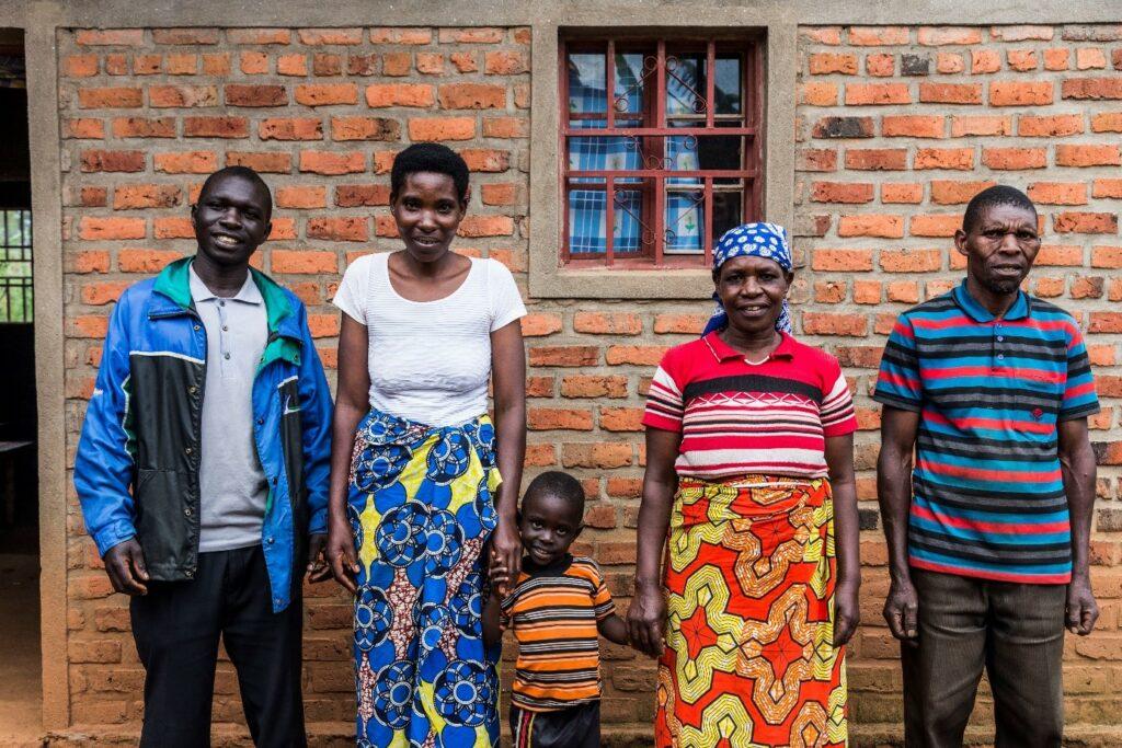 Zwei Frauen, zwei Männer, ein Kind stehen vor einer Hauswand. Die Frauen halten das Kind den Händen.